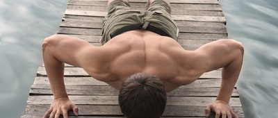 Man-doing-push-ups-on-deck-next-to-water